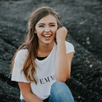 """Woman wearing shirt reading """"Femme"""" sits on hill, smiling."""